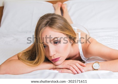 Sexy girl in white lace underwear lying on the bed, melancholic and daydreaming - stock photo