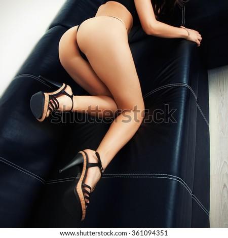 Sexy girl kneels on sofa - stock photo