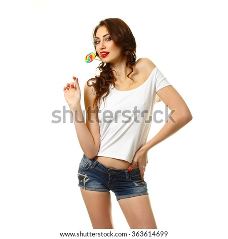 sexy girl licking a lollipop. Beautiful woman with creative makeup holding a candy. pretty smiling brunette girl with a lollipop in her hand - stock photo