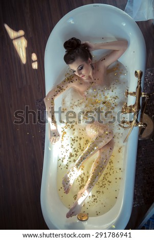 Sexy girl lying in the bath with foam - stock photo