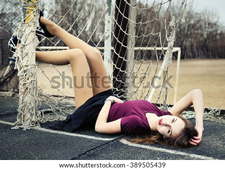Sexy girl lying in the gate on the football pitch - stock photo