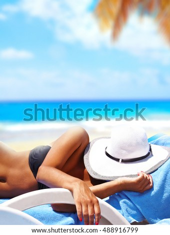 Sexy girl lying on a chaise lounge and sunbathe under the sun on a tropical beach in a hot summer day. Presentation of vacation and paradise leisure. Exotic tropical island in the ocean.