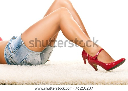 sexy girl lying on carpet with long legs in red shoes - stock photo