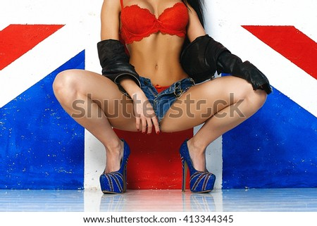 Sexy girl near the British flag. Stripped girl brunette. The girl with silicone breasts in red lingerie. Model with Stikine nipples. English style. Luxurious brunette girl in chert - stock photo