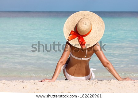 Sexy girl on tropical beach. Vacation. Woman in Sun Hat tanning and relaxing. - stock photo