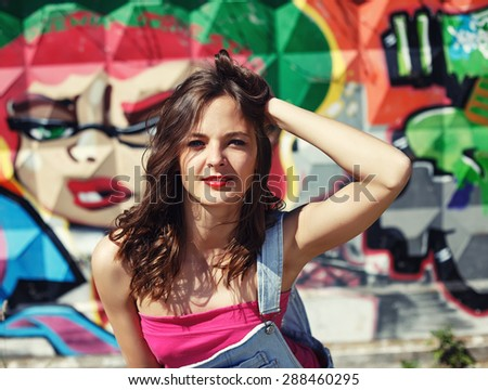 sexy girl outdoor summer fashion portrait. young beautiful female model in jeans shorts, white t-shirt and cap posing in extreme park - stock photo