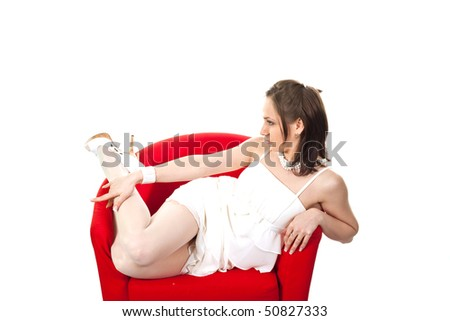 Sexy girl posing on red sofa isolated