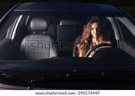 Sexy girl sit behind the wheel of the car and makes faces - stock photo
