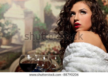 Sexy girl sit with wine in fur coat at evening - stock photo