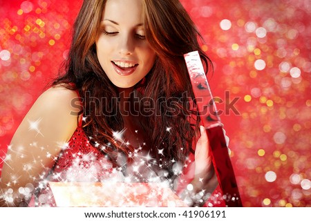 sexy girl smiles and holding a gift in magic packing - stock photo