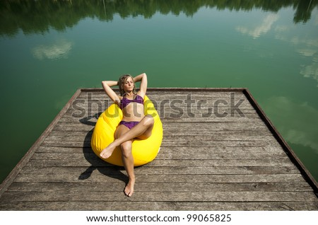 http://thumb7.shutterstock.com/display_pic_with_logo/100778/99065825/stock-photo-sexy-girl-sunbathing-on-the-yellow-beanbag-on-a-wooden-pier-99065825.jpg