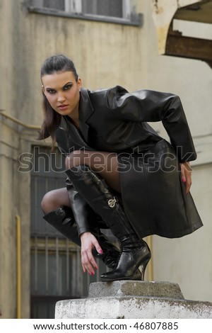 sexy girl vampire with black leather coat outside during night on the top of pilaster building - stock photo