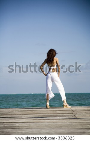 Sexy girl wearing a bikini top, white pants, and looking out over the ocean. - stock photo