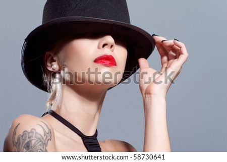 Sexy girl wearing a black hat, isolated on grey - stock photo