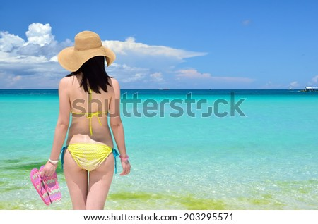 Sexy girl wearing a straw hat on the tropical beach enjoying summer holidays - stock photo