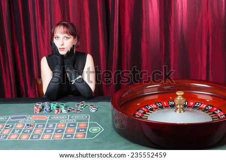 sexy girl wearing black dress and black gloves plays in a casino - stock photo