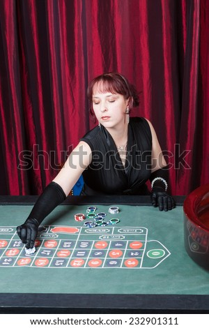 sexy girl wearing in a black dress and gloves plays in casino - stock photo