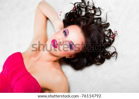 sexy girl wearing pink dress and lies on white fur - stock photo
