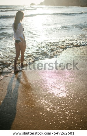 Sexy girl wearing white shit and bikini - walking in the sea