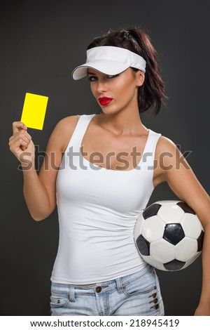 Sexy girl with a soccer ball and a yellow card - stock photo
