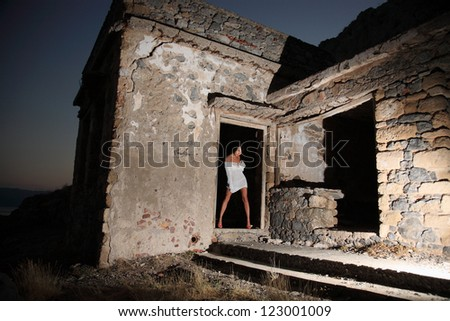 sexy girl with beautiful legs in the old house at night