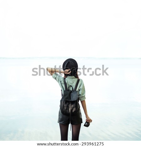 sexy girl with camera in hand on the beach - stock photo