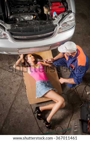 Sexy girl with long legs lying under car checking the engine and auto mechanic sitting near giving her tools at the car repair shop. Girl wearing high heels blue jeans skirt. View from the top - stock photo