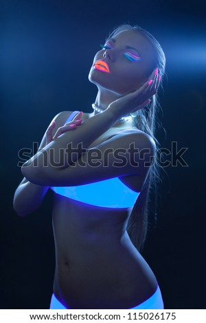 sexy girl with neon make-up dance in ultraviolet - stock photo