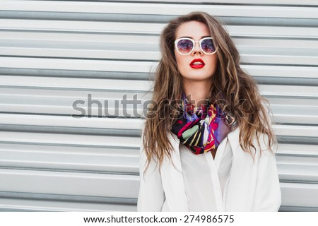 sexy girl with red lips on a background of a fence on a sunny day - stock photo