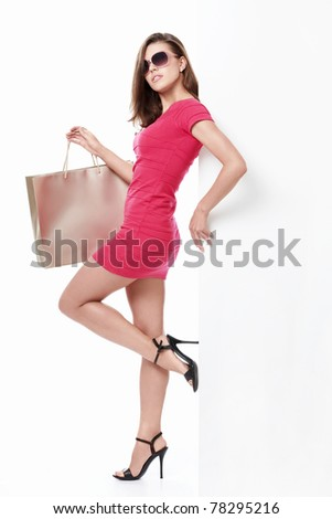 Sexy girl with shopping bags and empty the board on a white background - stock photo