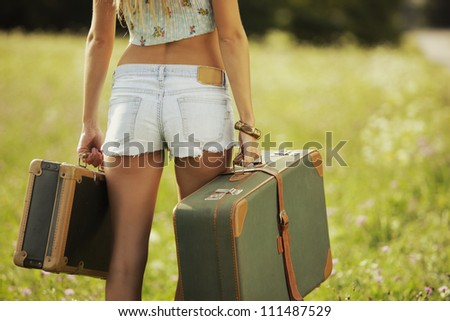 Sexy girl with suitcases, walking on a lawn - stock photo