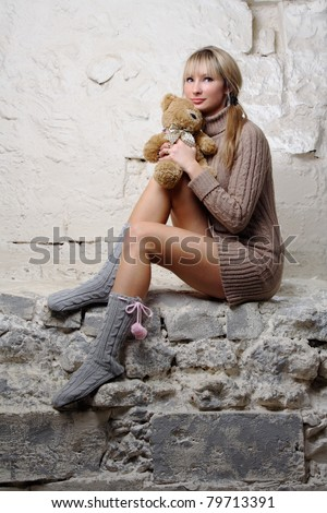 sexy girl with teddy bear sitting on wall in short erotic dress - stock photo