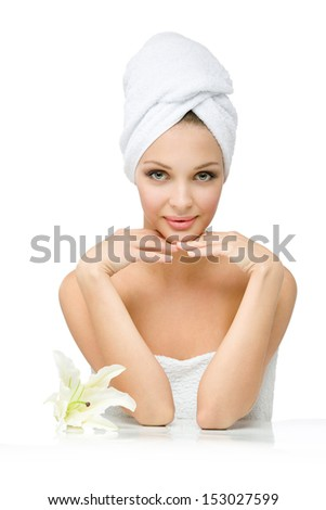 Sexy girl with towel on head touches her face sitting near white lily, isolated on white. Concept of healthcare, beauty and youth