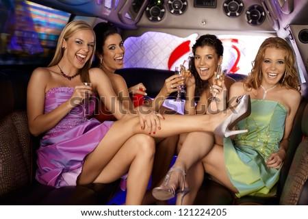 Sexy girls having party in limousine, smiling, drinking.