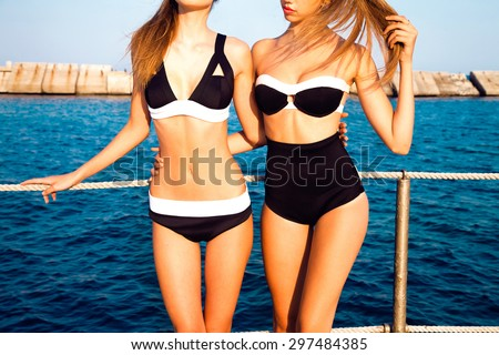 Sexy girls in bikini shows their stylish swimsuits,and having fun,enjoy weekends,friends on the beach,summer accessory,store,girls on beach party,slim fit body,perfect body,lingerie fashion,hipsters - stock photo