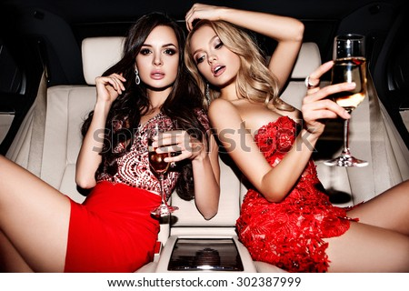 Sexy girls in the car.  Celebrating. - stock photo