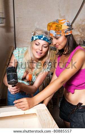 sexy girls in the carpentry shop carpenters - stock photo