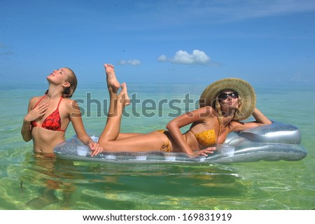 Sexy girls resting at mattress at tropical water - stock photo