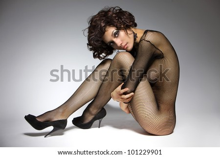 sexy glamor girl with curly hair in black clothes, sitting and hugging himself with his hands behind his knees - stock photo