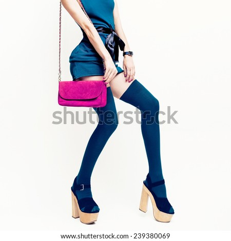 Sexy Glamorous Lady in the green dress and stockings on white background. Pink clutch. Fashion accessories. - stock photo