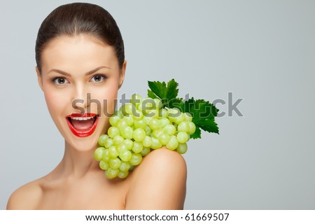 Sexy grape. A pretty sexy lady holding a bunch of grape on her nude shoulder. - stock photo