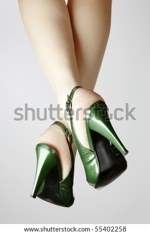 Sexy green leather high heels stilettos shoes and womens legs - stock photo