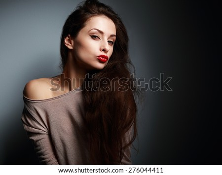 Sexy grimacing young woman with red lipstick showing kissing sign on dark background - stock photo