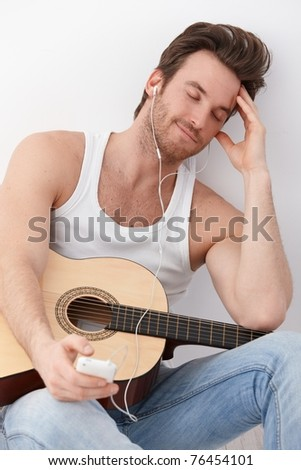 Sexy guitar player sitting on floor, listening to music through headphones, having mp3 player, smiling. - stock photo