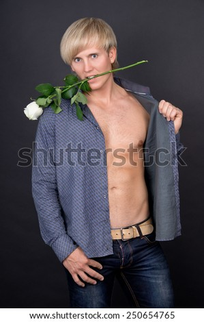 Sexy guy with an open-chested and a rose in teeth - stock photo