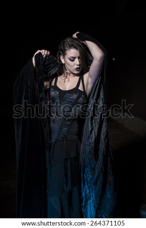 Sexy halloween, Sensual young girl dressed in black coat with gothic style - stock photo