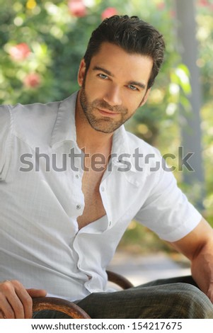 Sexy handsome man outdoors with playful smile - stock photo