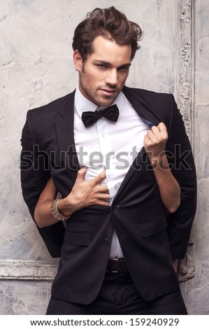 Sexy handsome nab in classical costume. Female hands unbutton his coat and shirt  - stock photo