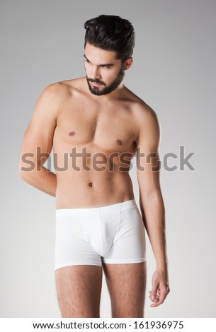 sexy handsome naked man in underwear posing in the studio - stock photo