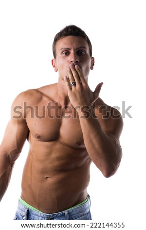 Sexy handsome shirtless man with a muscular physique standing blowing a kiss with his hand to his mouth or hiding a guilty expression, isolated on white - stock photo